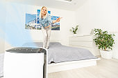 air purifier in room for clean and fresh air with woman stretching hands and relax in background