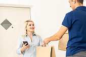 woman receiving boxes from postman at the door in home delivery concept. Woman received the parcel from the postman at home. Postman giving cardboard box to young woman.