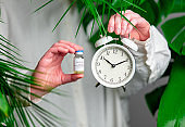 female hand holding alarm clock and vaccine in a bottle on background with palm leaves