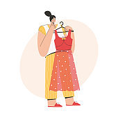 Woman thinking and holding fashionable dress on hanger