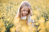 Pretty young toddler walk in flower field outdoors