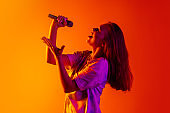 Side-viewed cropped portrait of young beautiful caucasian girl singing with microphone on gradient yellow red background