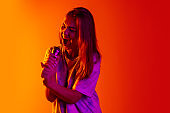 Cropped portrait of young beautiful caucasian girl expressively singing with microphone on gradient yellow red background