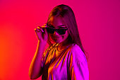 Cropped stylish young caucasian girl wearing black fashionable sunglasses isolated on neon background