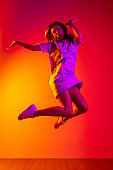 Joyfully jumping. Full-length portrait of young beautiful girl in motion isolated on colorful yellow pink red background in neon