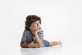 Portrait of little preschool boy posing isolated over white studio background.