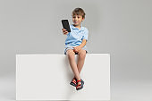 One Caucasian little boy in casual clothes sitting on box isolated over gray studio background.