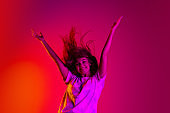 Full-length portrait of young beautiful girl in motion with hands up isolated on colorful yellow pink red background in neon