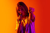 Cropped portrait of young beautiful caucasian girl singing with microphone on gradient yellow red background