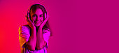 Beautiful young caucasian girl listening to music in headphones isolated on pink background in neon