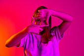 Portrait of young beautiful caucasian girl isolated on pink neon background