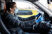 Pretty caucasian woman with glasses, anti virus medical mask and blue latex gloves driving a car with her hands on the steering wheel.