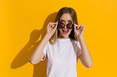 Excited Young Woman Is Looking Over Sunglasses And Talking