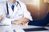 Unknown man-doctor reassuring his female patient, close-up. Two physicians consulting and giving some advices to woman. Concepts of medical ethics and trust. Empathy in medicine