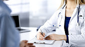 Unknown woman-doctor is prescribing some antibiotics for her patient, while they are sitting at the desk in the cabinet in a clinic. Female physician with a stethoscope is writing at clipboard, close-up. Perfect medical service in a hospital