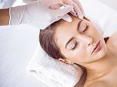 Beautician doing beauty procedure with syringe to face of young brunette woman in sunny spa center. Cosmetic medicine and surgery, beauty injections