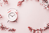 Spring time background. May flowers and April floral nature with alarm clock on pink. Branches of blossoming apricot macro with soft focus. For easter greeting cards with copy space. Springtime.