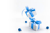 Holiday winter blue. White gift box with blue ribbon, New Year balls in Christmas composition on white background for greeting card. Copy space. Winter holidays, New Year.