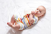 Baby with baby milk bottle. Light background.
