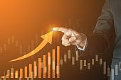 business success concept. businessman finger touch up trend arrow with bar graph and candle stick on virtual screen