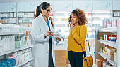 Pharmacy: Professional Caucasian Pharmacist Helping Beautiful Black Female Customer with Medicine Recommendation, Advice, Talking. Drugstore with Full of Drugs, Pills, Health Care, Beauty Products