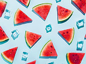 Summer refreshment arrangement watermelon triangle slices and ice cubes on light blue background. Creative food photography. Flat lay, top view.