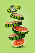 Summer fruit arrangement with slices of watermelon falling down stacked on a light green background. Creative food concept.