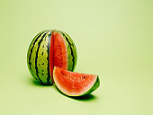 Fresh and juicy watermelon with a cut slice isolated on a pastel green background. Summer healthy refreshment. Creative tropical fruit or vegetable food concept.