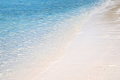 Clear sea waves and white sandy beach in summer.