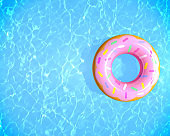 Top view summer background. Inflatable rubber donut ring floating on blue water in swimming pool with copy space, 3d rendering