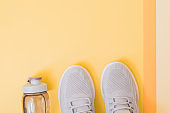 Concept of healthy lifestyle. Flat lay sport shoes, new sneakers on a yellow background