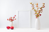 Home interior with decor elements. Mockup with a white frame, colorful autumn leaves and red berries in a vase on a light background