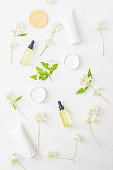 Flat lay pattern with cosmetics and jasmine flowers on a light background