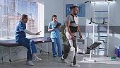 Man in exoskeleton learning to walk on treadmill near doctors