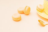 Yellow macaroons on a table with a yellow cup and saucer