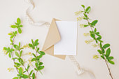 Mockup white wedding invitation and envelope with branches and green leaves on color background