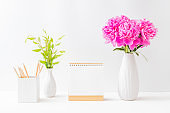 Mockup white desk calendar and pink peonies in a vase on a light background