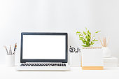 Home office workspace with laptop mockup and branches with green leaves in a vase, office supplies, desk calendar on a light background