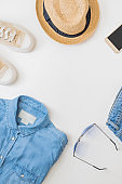 Flat lay summer composition with a straw hat, jeans and sneakers on a white background