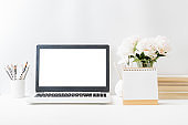Home office workspace with laptop mockup and white peonies in a vase, office supplies, desk calendar on a light background