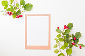 Flat Lay mockup blank paper sheet card with red berries and green leaves on white background