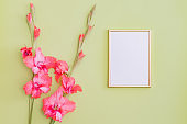 Mockup with a gold frame and pink flowers on a green background