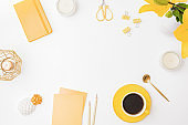 Flat lay workspace with notebook, cup of coffee and yellow lilies on white background