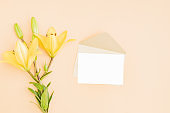 Mockup white wedding invitation and envelope with yellow lilies on color background