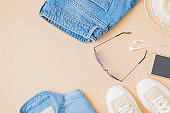 Flat lay summer composition with a straw hat, jeans and sneakers on a yellow background