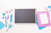 Black chalkboard mockup with flat lay school and office supplies on a white background