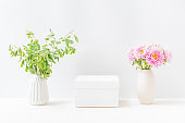 Empty white box and pink flowers in a vase on a light background. Mockup banner, podium for display of advertise product