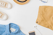 Flat lay summer composition with a straw hat, denim and sneakers on a white background
