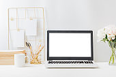 Home office workspace with laptop mockup and mood board, books, office supplies on a light background
