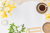 Flat lay home office desktop with notebook, yellow irises, cup with coffee on a white background